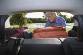 Hombre poner equipaje — Foto de Stock