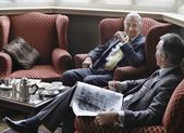 Business men sitting in lobby and talking — Stock Photo