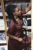 Office worker on ladder in file storage room — Foto de Stock
