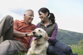 Couple and golden retriever resting — Stock Photo