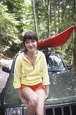 Woman sitting on car bonnet — Stock Photo