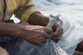Local fisherman fixes holes and tangles — Stock Photo