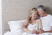 Couple drinking champagne in bed — Stock Photo
