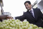 Business man paying fruit merchant — Stock Photo