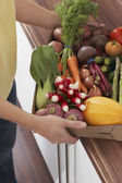 Woman holding container of fresh vegetables — Stock Photo