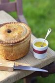 Pork pie, knife and cup of mustard — Stock Photo