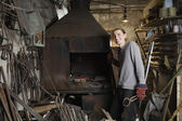 Blacksmith standing by forge in workshop — Stock Photo