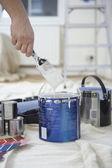 Man dipping paint brush — Stock Photo