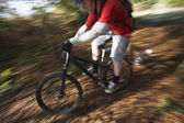Dog chasing man on mountain bike — Stock Photo