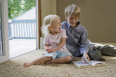 Boy with sister sitting on carpet — Photo