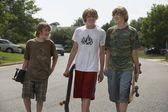 Brothers walking on street carrying skateboards — Stock Photo