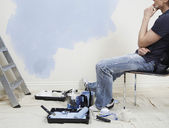 Man resting while painting wall — Stock Photo