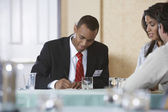 Business man writing at conference meeting — Stock Photo