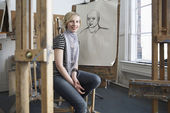 Artist sitting in front of charcoal portrait — Stock Photo