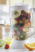 Blender filled with fresh fruits — Stock Photo
