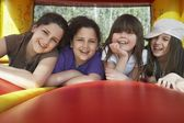 Girls lying in row in bouncy castle — Stock Photo