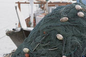 Fishing nets piled high on boat — Stock Photo