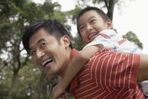 Father giving son piggyback — Stock Photo