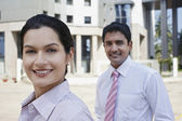 Businessman and businesswoman smiling — Stock Photo