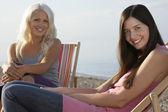 Women sitting on deckchairs — Stock Photo