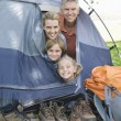 Family smiling from a tent — Stock Photo #33893217