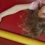Girl lying down in bouncy castle — Stock Photo #33896307