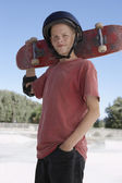 Boy holding skateboard — Stock Photo