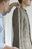 Tailor measuring jacket sleeve — Stock Photo