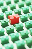 Green model houses with one red — Stock Photo