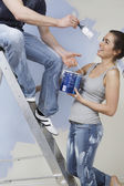 Man on ladder trying to paint woman — Stock Photo