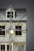Small model of house chained — Stock Photo