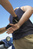 Police man putting handcuffs — Stock Photo