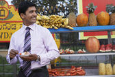 Businessman standing in front of fruit stall — Stock Photo