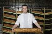 Baker Carrying Loaves of Fresh Bread — Stock Photo