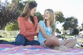 Mother and daughter sitting on picnic blanket — Stock Photo
