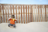 Boy sitting against wooden fence — Stock Photo