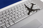 Shadow of jumbo jet over keyboard — Stock Photo
