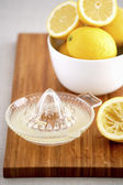 Bowl of lemons and juicer on cutting board — Stock Photo