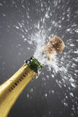 Champagne bottle popping cork — Stock Photo