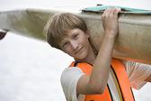 Boy carrying kayak — Stock Photo