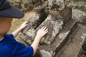 Child Looking at Feet of Ancient Statue — Stock Photo