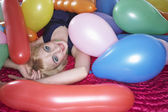 Girl lying on bed under balloons — 图库照片