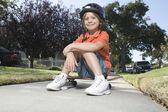 Boy sitting on skateboard — Stock Photo