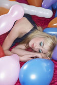 Girl  lying on bed surrounded by balloons — Stock Photo