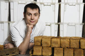 Baker With Loaves of Fresh Bread — Stock Photo