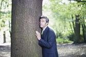 Businessman pressing against tree — Stock Photo