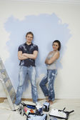 Couple resting while painting wall — 图库照片