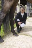 Girl grooming horse's leg — Stock Photo