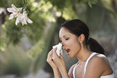 Woman sneezing under tree — Stock Photo