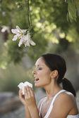 Woman sneezing under tree — Stock Photo